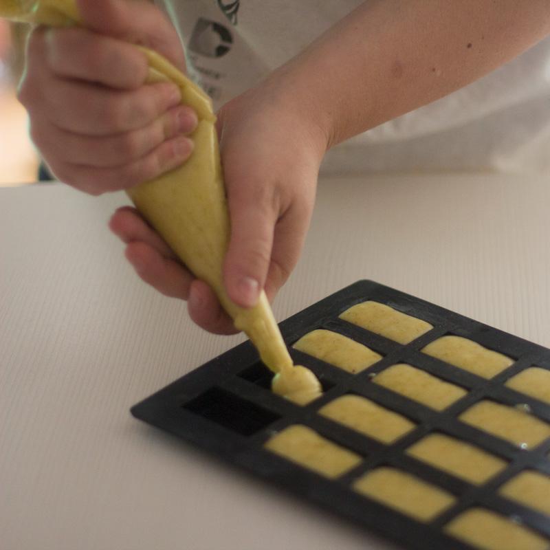 repartiendo la masa de los financieros de pistachos en el molde
