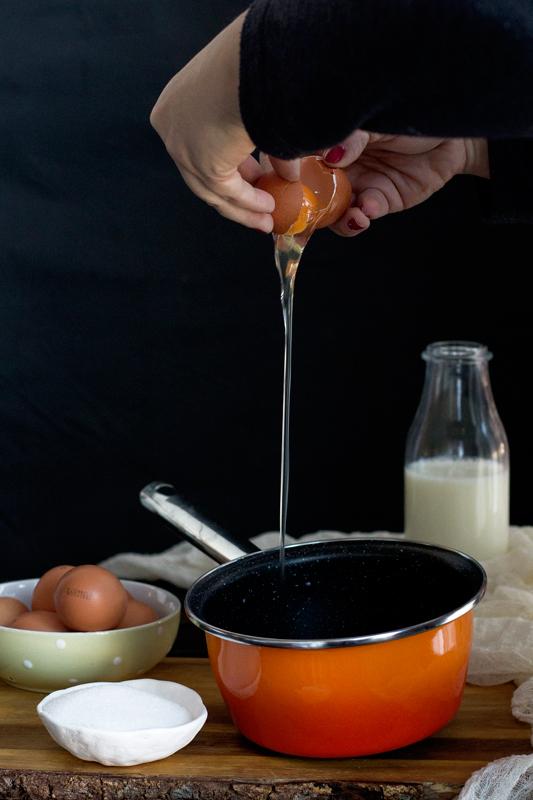 echando huevo en la crema pastelera para las berlinas rellenas de crema pastelera. receta paso a paso